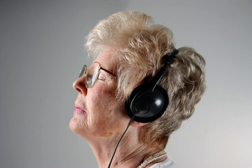 older woman listening to music in headphones