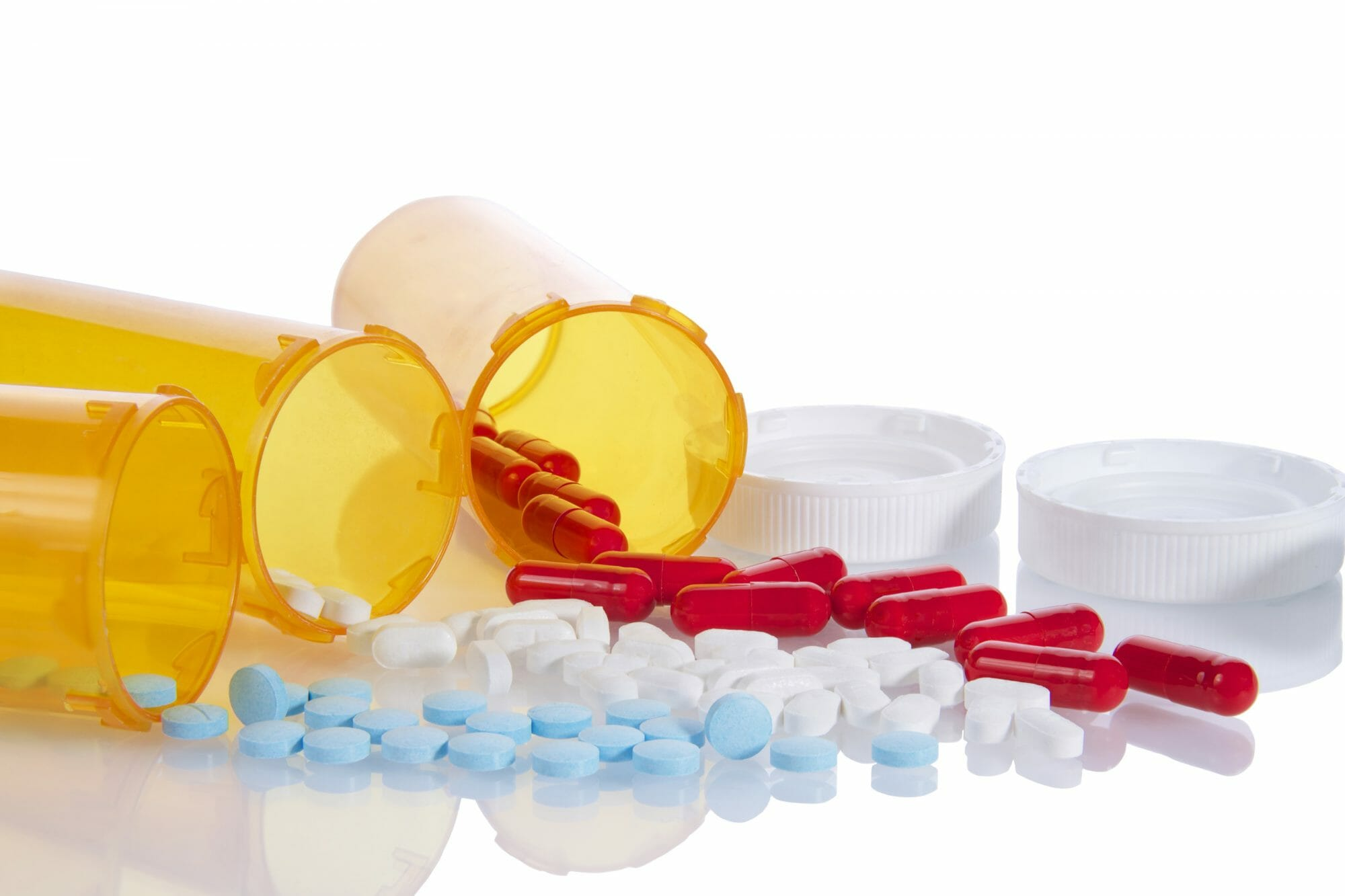 Three Prescription bottles lined up on their sides spilling medication pills out
